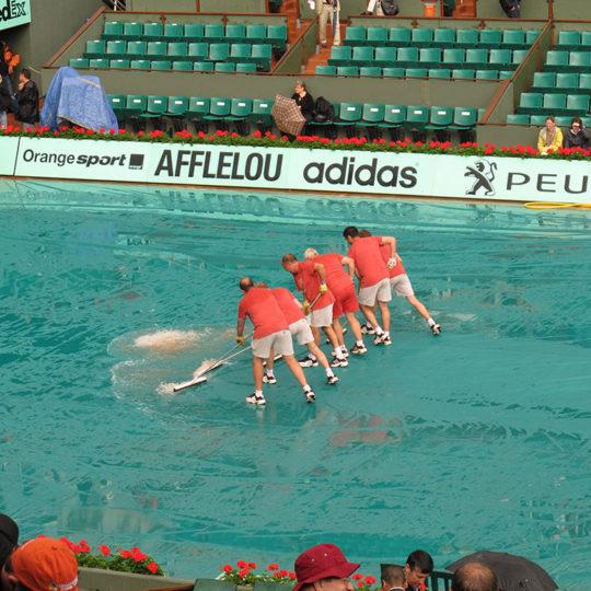 Roland Garros'ta yağmur dinmiş, görevliler yağmur sularını temizliyorlar